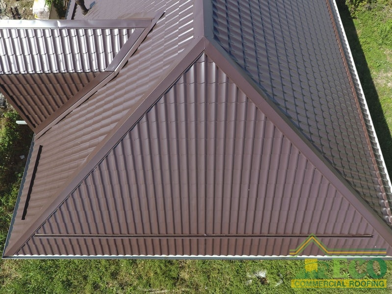 The roof of corrugated sheet. Roofing of metal profile wavy shape. A view from above on the roof of the house.